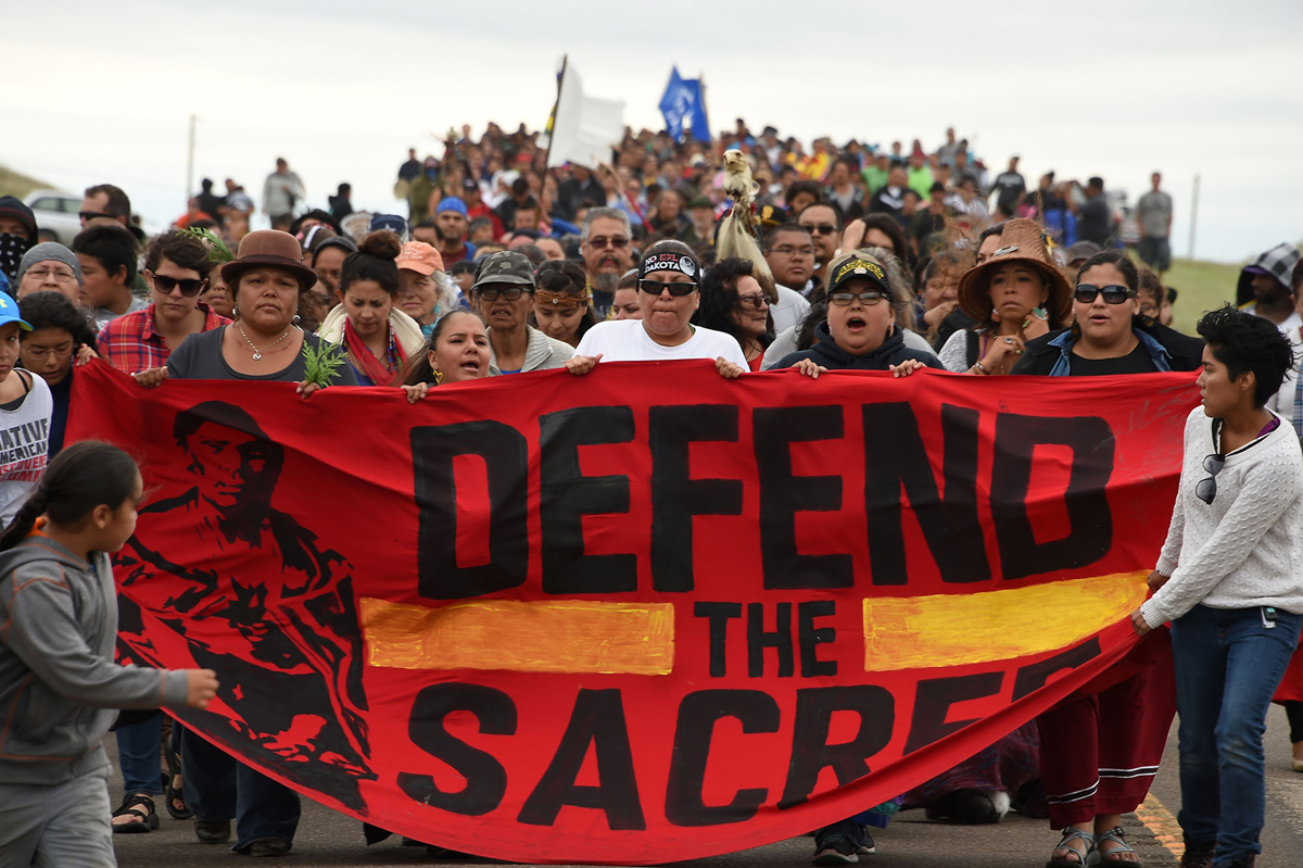 Native Americans march to a burial ground sacred site that was disturbed by bulldozers building the Dakota Access Pipeline (DAPL), near the encampment where hundreds of people have gathered to join the Standing Rock Sioux Tribe's protest of the oil pipeline that is slated to cross the Missouri River nearby, September 4, 2016 near Cannon Ball, North Dakota.Protestors were attacked by dogs and sprayed with an eye and respiratory irritant yesterday when they arrived at the site to protest after learning of the bulldozing work. / AFP / Robyn BECK        (Photo credit should read ROBYN BECK/AFP/Getty Images)