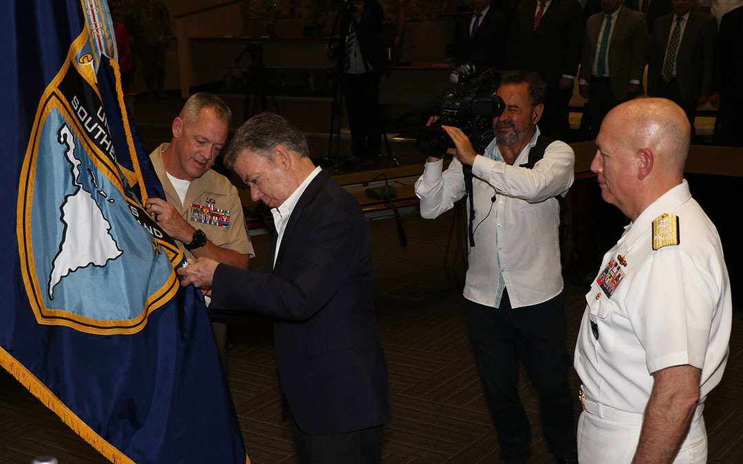 MIAMI -- Colombian President Juan Manuel Santos pins the Orden of San Carlos (Order of San Carlos) Medal to the U.S. Southern Command (SOUTHCOM) flag while U.S. Navy Adm. Kurt W. Tidd, commander of U.S. Southern Command, and U.S. Marine Corps Sgt. Maj. Bryan Zickefoose, SOUTHCOM command sergeant major, look on. Santos visited the military headquarters April 25 to thank its personnel and present the command with the medal for SOUTHCOM's unwavering support for Colombia's peace and security. (Photo by Jose Ruiz)
